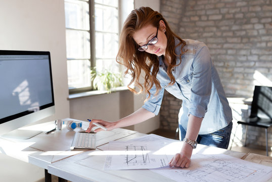 Female designer in office working on architects project