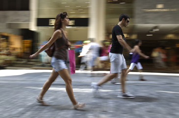 People walk along a commercial street in central Athens