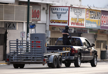 Policeman stands guard on the bed of a truck towing a special container away from a hotel during an operation in downtown Monterrey