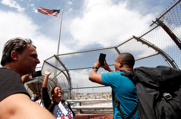 Cuban migrants take a photo in front a U.S flag after arriving by plane from Panama to Mexico, as they make their way to the U.S., in Ciudad Juarez, at the Mexican border crossing with El Paso