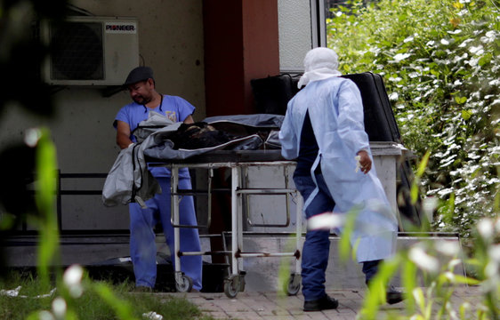 FILE PHOTO - Staff work next to the body of an inmate, who died during a prison riot, at the Medical Legal Institute in Manaus