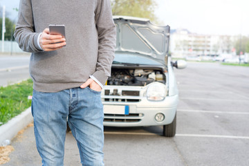 Man calling mechanic after car breakdown