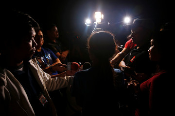 A woman related to a suspected drug addict who was shot dead by unknown gunmen, talks to reporters shortly after the killing in Manila