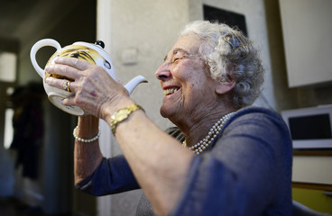 "British children's writer and illustrator Judith Kerr drinks from a tea pot as she recreates a scene from her bestselling picture book ""The Tiger Who Came To Tea"", in London"