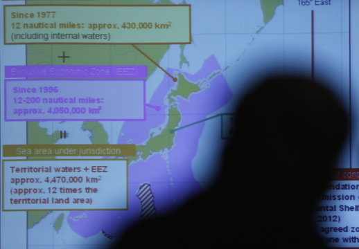 A projected map of Japan's territorial waters are seen through a reporter's silhouette during a news conference by Japan Coast Guard Commandant Takashi Kitamura, in Tokyo