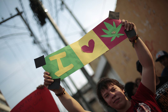 """A man holds a sign which reads, """"I Love Marijuana"""" during a demonstration supporting the legalization of marijuana in Guatemala City"""