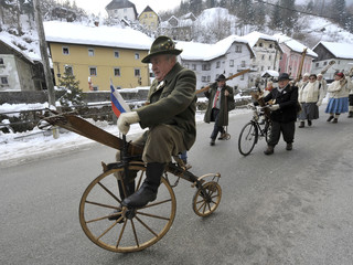 A man carries old-fashioned ski equipment as he cycles on a homemade bicycle with a group of skiers, through the village of Kropa