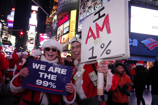 A couple holds banners linked with Occupy Wall Street movement as they gather in Times Square during the annual SantaCon celebration in New York