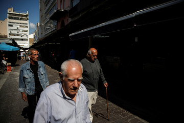 People walk at the main food market in central Athens