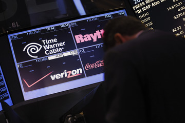 A trader passes by the post that trades Verizon wireless and Time Warner Cable on the floor of the New York Stock Exchange