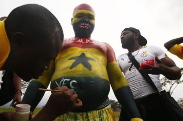 Soccer fans paint Misugha, a popular Ghana supporter, before their quarter-final soccer match of the 2015 African Cup of Nations against Guinea in Malabo