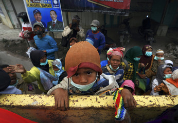 A child climbs onto a truck during an evacuation as ash from Mount Sinabung volcano hit Payung village in Karo