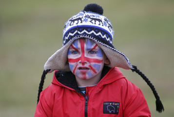A boy with a Union Jack flag painted on his face attends a parade in Stanley