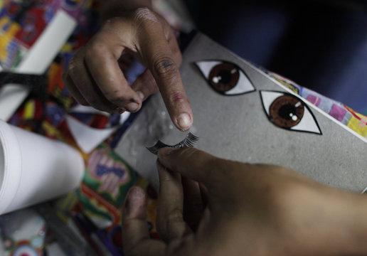 Adriana Ramirez puts glue on fake eyelashes to be used for a pinata depicting TV celebrity Kim Kardashian at her brother's workshop in Reynosa