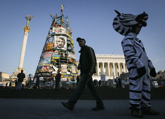 Man and entertainer in zebra costume stand near artificial New Year tree with attached picture depicting Russian president Putin in Kiev