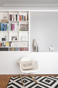 Salon et bibliothèque avec chaise à bascule design blanche, tapis à motif noir&blanc, et vases argenté et livres d'art