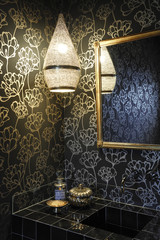 Black bathroom with black and gold floral wallpaper, Moroccan lamp with subdued light and black tiles