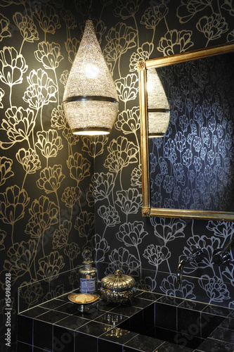 Black Bathroom With Black And Gold Floral Wallpaper Moroccan Lamp