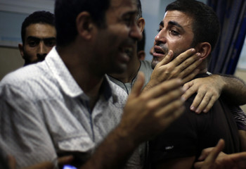 Relatives of Palestinians, whom medics said were killed in an Israeli air strike on their van, grieve at a hospital in Gaza City