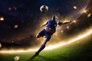 fat soccer player in action. stadium in fire night