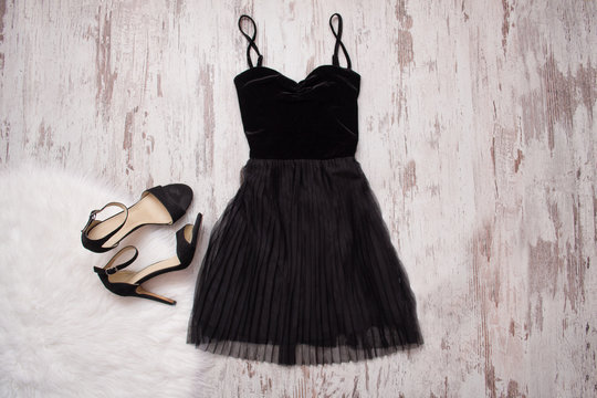Little black dress and black shoes. Wooden background, fashionable concept