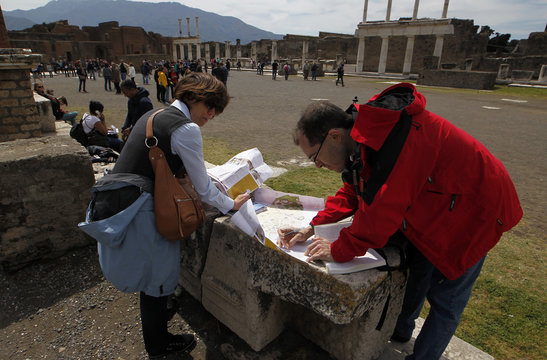 People check a map as they visit the ruins at the ancient archaeological site of Pompeii