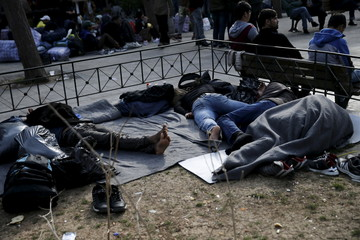 Migrants sleep on Victoria Square, where stranded refugees and migrants, most of them Afghans, find shelter in Athens