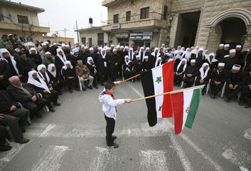 A boy holds flags of Iran and Syria during a rally in Majdal Shams on the Golan Heights