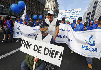 """A Belgian police officer sitting in a wheelchair holds a placard reading """"Get the thief"""" during a demonstration in central Brussels"""