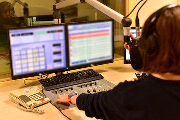 young female presenter in radio station hosting show for radio live in Studio