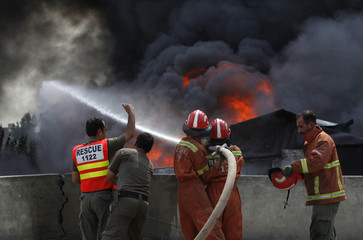 Firefighters work to put out a blaze in a warehouse of the United Nations High Commissioner for Refugees (UNHCR) in Peshawar
