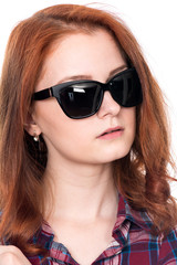 Close-up portrait of a red-haired beautiful woman wearing sunglasses