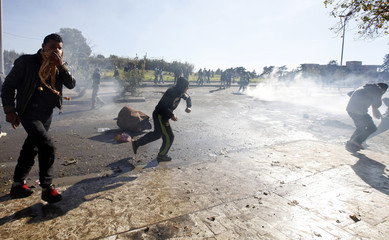 Protesters run to hide from tear gas canisters during clashes with riot gendarmerie in Cheraga on the outskirts of Algiers
