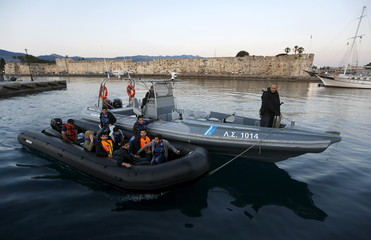 A dinghy with Syrian refugees is towed into the port of Kos