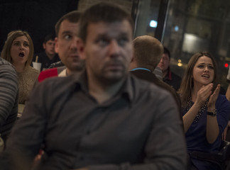 Ukrainian soccer fans react after France's Benzema scored a goal during their return leg playoff match for the qualification to the World Cup finals, as they watch the match in a pub in Kiev