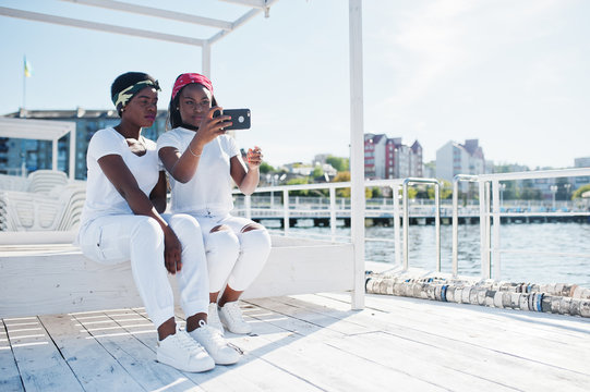 Two stylish and trendy african american girls, wear on white clothes against lake on pier beach making selfie from cell phone. Street fashion of young black people.