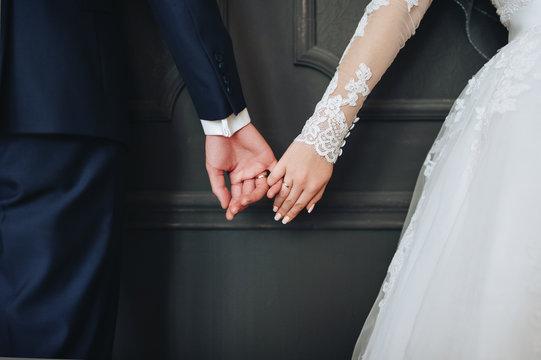 Newlyweds hold hands. Grey background.