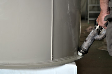 Big cylindrical custom made plastic tank in the process of polishing and plastering