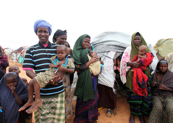 A displaced family from Somalia stand in front of their makeshift shelter in south Mogadishu in Hodan district