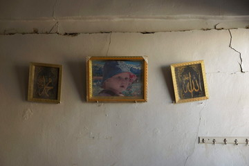 A picture hangs between framed Arabic calligraphy on a damaged wall at a site hit by what activists said were airstrikes by forces loyal to Syria's President Bashar al-Assad in Sheikh Meskeen
