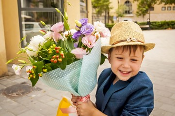 Cute Caucasian kid wearing a straw hat and a trendy jacket with a flower bouquet stock image.