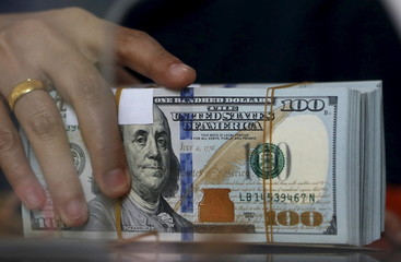 An employee of a money changer holds a stack of U.S.  Dollar notes before giving it to a customer in Jakarta