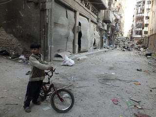 A boy holds a bicycle near debris and damaged buildings in Homs