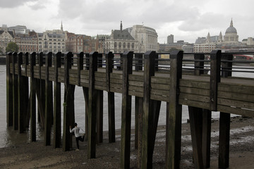 A man stretches by the River Thames on the South Bank in central London
