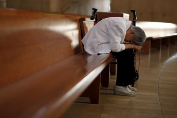 Han Kyu Lim, 83, holds a rosary as she prays in the Cathedral of Our Lady of the Angels in Los Angeles