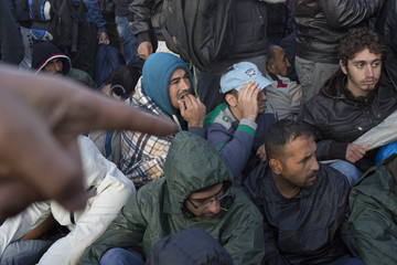 Migrants wait in front of a registration camp in Opatovac