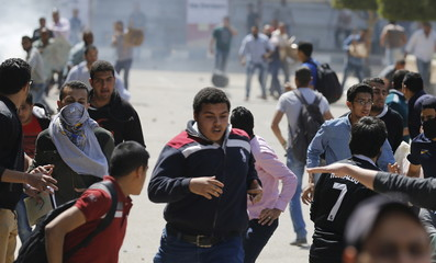 Cairo University students who are supporters of the Muslim Brotherhood and ousted President Mohamed Mursi run and flee during clashes with administrative security personnel during a protest in Giza