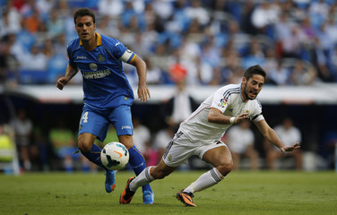 Real Madrid's Isco is tackled by Getafe's Pedro Leon during their Spanish first division soccer match at Santiago Bernabeu stadium in Madrid