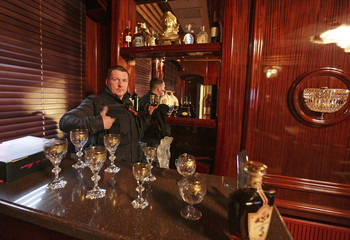 A man gestures behind the interior bar inside the residence as anti-government protesters and journalists walk on the grounds of the Mezhyhirya residence of Ukraine's President Viktor Yanukovich in the village Novi Petrivtsi outside Kiev