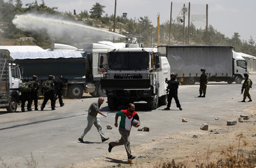 A Palestinian protester runs as Israeli border police fire a water cannon during a protest outside Israel's Ofer military prison